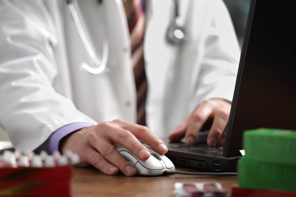 médico com um mouse de computador